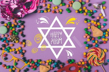 top view of arranged masquerade masks, candies and cookies isolated on purple, purim holiday concept