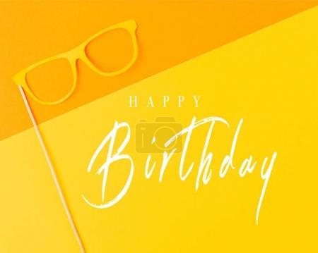 vue de dessus du masque de mascarade sur fond jaune et orange, inscription joyeux anniversaire