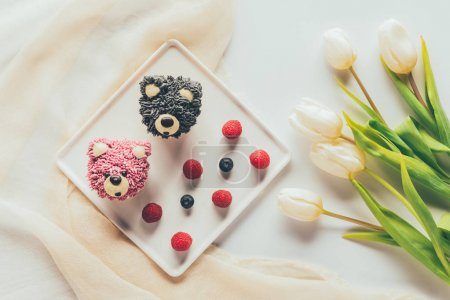 top view of delicious muffins in shape of bears, fresh berries and tulip flowers