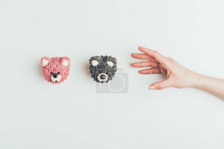Photo pour Recadrée coup de main et de délicieux gâteaux en forme d'ours isolé sur fond gris - image libre de droit