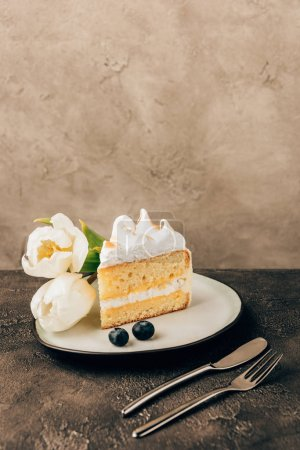 delicious piece of cake with whipped cream, fresh blueberries and tulips on plate