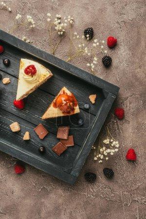 Photo pour Vue de dessus des gâteaux sucrés savoureux avec chocolat et baies sur plateau en bois - image libre de droit