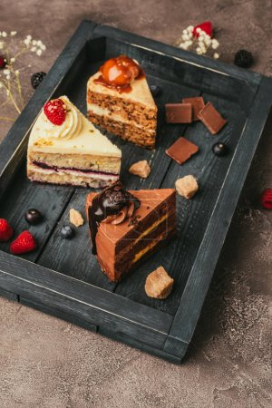 close-up view of pieces of delicious cakes on wooden tray