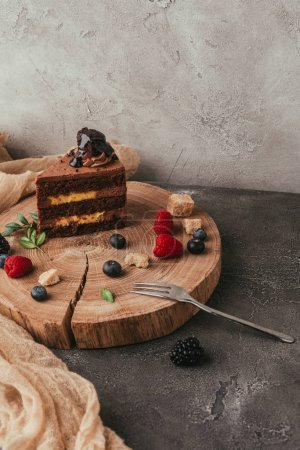 Photo for Close-up view of delicious chocolate cake with berries on wooden board - Royalty Free Image