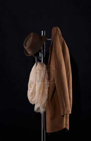 classic coat, hat and scarf hanging on coat rack isolated on black