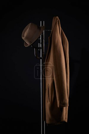 hat and classic jacket hanging on coat rack isolated on black