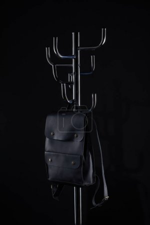 black leather backpack hanging on coat rack isolated on black