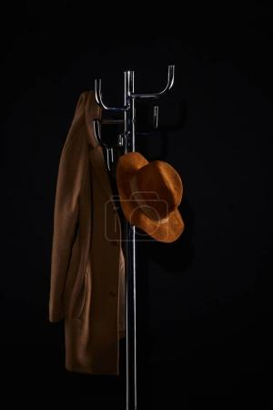 hat and coat hanging on coat rack isolated on black