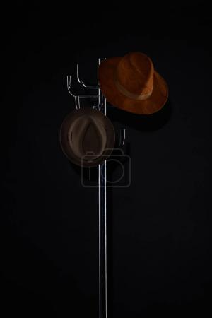 Photo for Hats hanging on coat rack isolated on black - Royalty Free Image