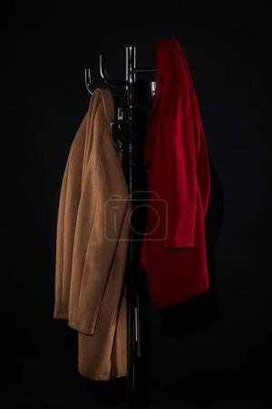 Photo pour Manteaux classiques sur porte-manteau isolée sur fond noir - image libre de droit