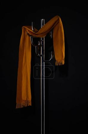 yellow scarf hanging on coat rack isolated on black