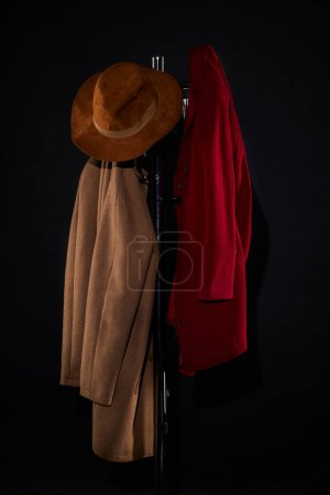 Photo for Coats and hat hanging on coat rack isolated on black - Royalty Free Image