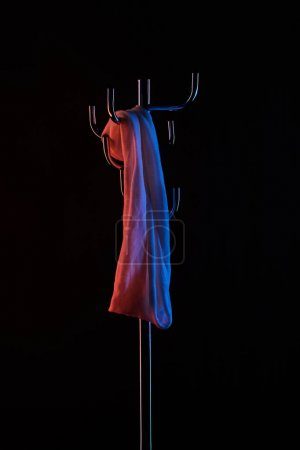 cloth hanging on coat rack under toned light isolated on black