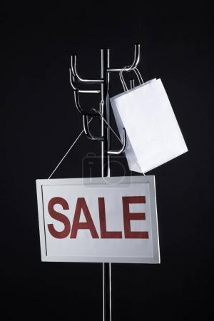 sale signboard and paper bag on coat rack isolated on black