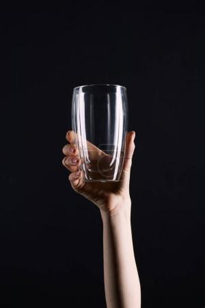 cropped shot of woman holding empty glass isolated on black