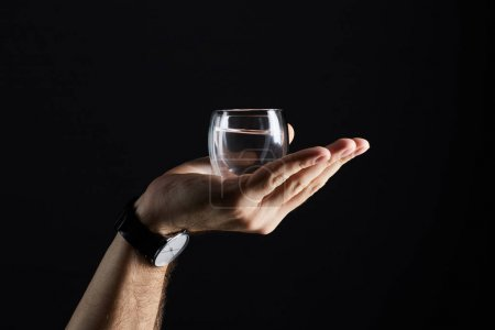 cropped shot of man holding glass of liquid isolated on black