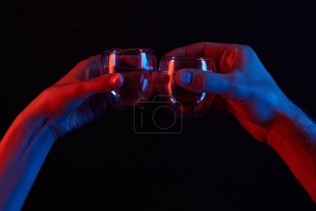cropped shot of man and woman clinking glasses under toned light isolated on black