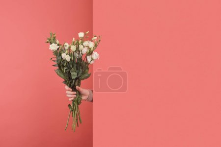 Photo for Woman sticking out white eustoma bouquet behind wall on red - Royalty Free Image