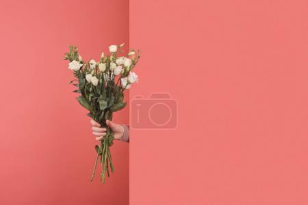 Woman sticking out white eustoma bouquet behind wall on red