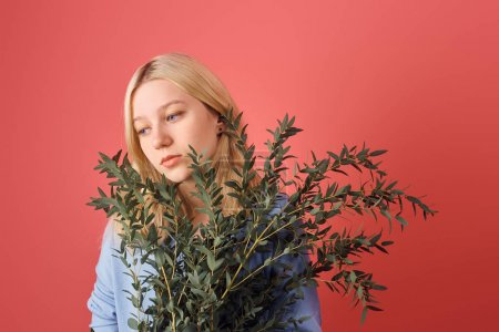 thoughtful young woman with bunch of eucalyptus branches isolated on red