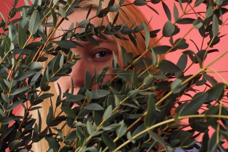 close-up shot of young woman hiding behind bunch of eucalyptus branches