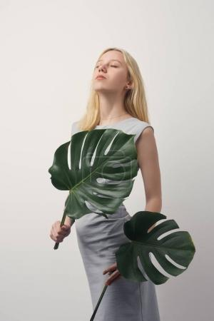 beautiful young woman with monstera leaves isolated on white