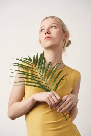 thoughtful young woman with palm branch looking up isolated on white