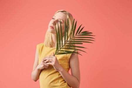 thoughtful young woman with palm branch isolated on red