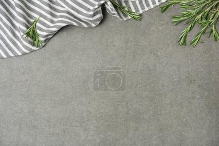 Photo for Flat lay with rosemary twigs and striped linen on grey concrete surface - Royalty Free Image
