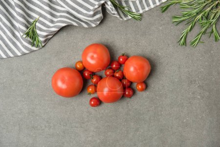 top view of ripe fresh tomatoes on grey concrete surface with linen and rosemary