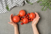 cropped shot of female hands holding ripe tomatoes on grey concrete surface with linen and rosemary