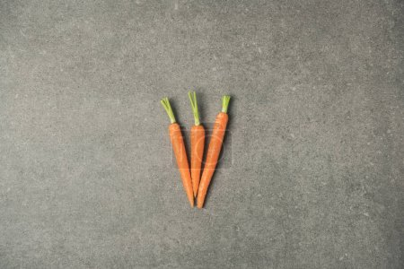 top view of arranged ripe carrots on grey concrete surface