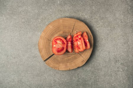 Photo for Top view of cuted tomato on wooden stump on grey concrete tabletop - Royalty Free Image