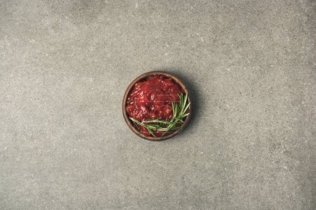 top view of sauce with rosemary twig served in bowl on grey concrete tabletop