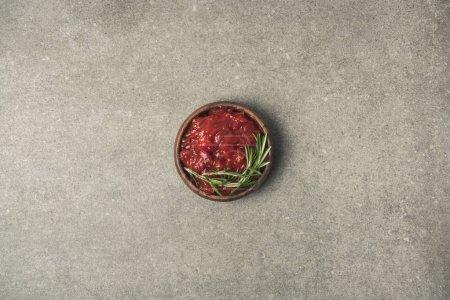 Draufsicht auf Sauce mit Rosmarinzweig, serviert in Schüssel auf grauer Betonplatte