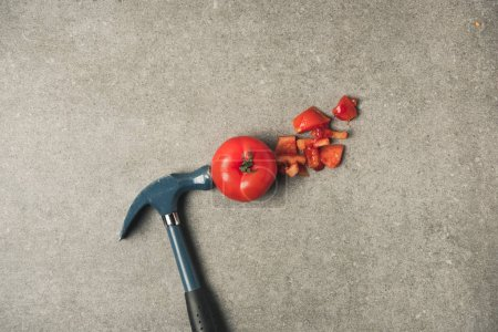 flat lay with cut fresh tomato, tomato pieces and hammer on grey concrete teblatop
