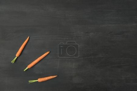 top view of arranged ripe carrots on dark surface