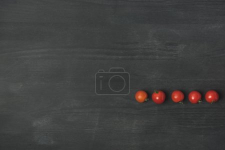 Photo pour Top view of arranged cherry tomatoes on dark grey surface - image libre de droit