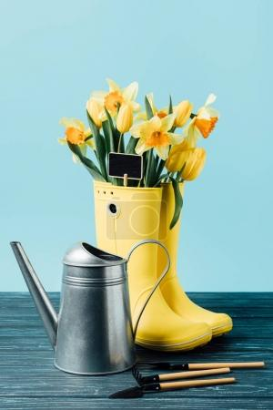 close up view of yellow bouquet of flowers and empty blackboard in rubber boots with watering can and gardening tools on wooden surface on blue