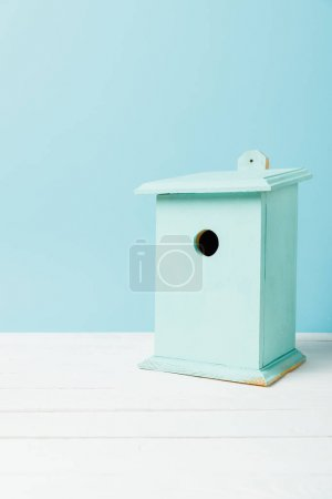close up view of blue birdhouse on wooden surface isolated on blue