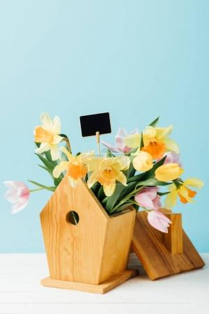 Photo for Close up view of beautiful bouquet of flowers with blank chalkboard in birdhouse on wooden tabletop isolated on blue - Royalty Free Image