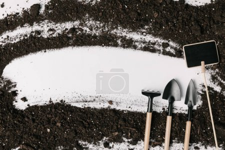 top view of arranged gardening equipment, empty blackboard and soil isolated on white