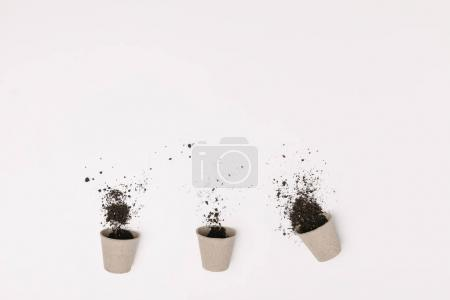 top view of three flowerpots with ground isolated on white