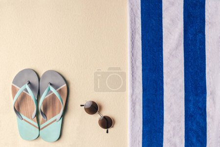 Flip flops and sunglasses by towel on sandy beach