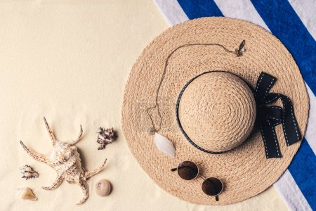 Straw hat with sunglasses and seashells on sandy beach