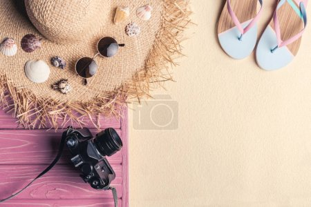 Straw hat with flip flops and camera on light sand
