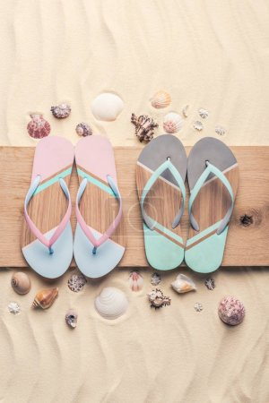 Flip flops and seashells on wooden pier on light sand