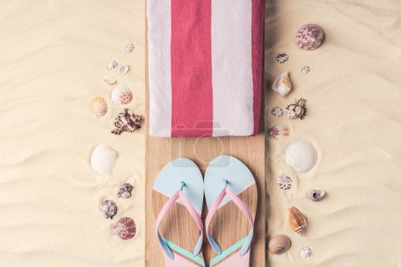 Flip flops and towel with shells on light sand