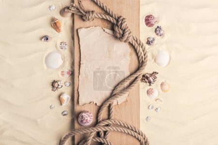 Photo for Summer travel template with seashells and rope on wooden pier on light sand - Royalty Free Image