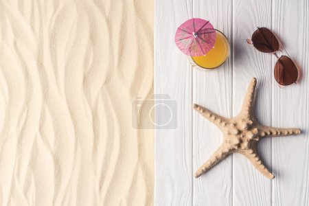 Cocktail with starfish and sunglasses on sandy beach
